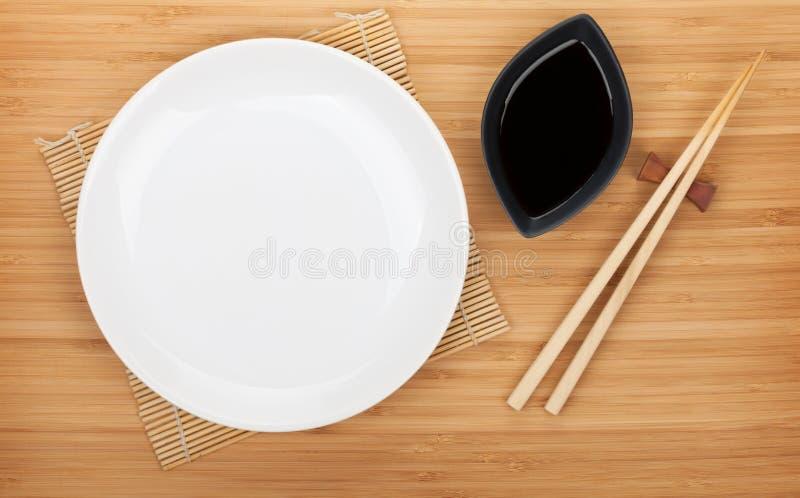 Leere Platte, Sushiessstäbchen und Sojasoße lizenzfreies stockbild