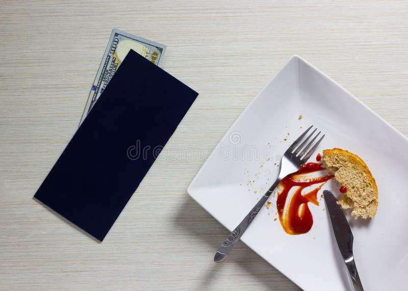 Leere Platte verließ nach dem Abendessen mit Rechnung und Dollar Anmerkung auf Holz stockbilder