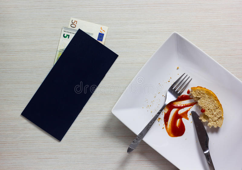 Leere Platte verließ nach dem Abendessen mit Rechnung und Euroanmerkung auf hölzernem stockfotos