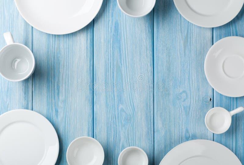 Leere Platten und Schüsseln auf blauem hölzernem Hintergrund stockbild
