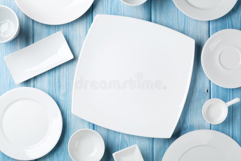 Leere Platten und Schüsseln auf blauem hölzernem Hintergrund stockfoto