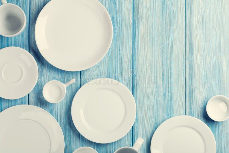 Leere Platten und Schüsseln auf blauem hölzernem Hintergrund lizenzfreie stockbilder