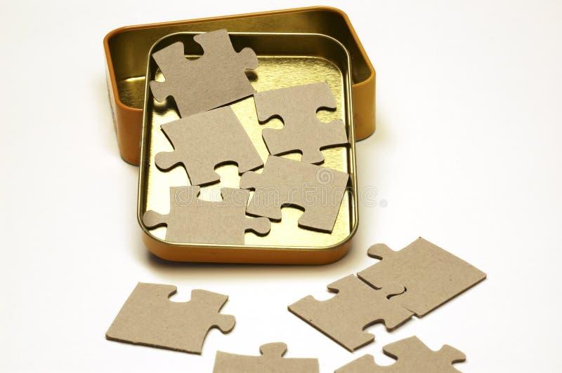 Leere Puzzlespiel-Stücke und Tin Box lizenzfreie stockfotografie