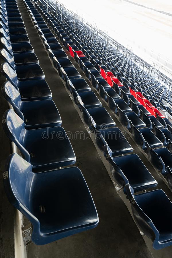 Leere Reihen von Stadionshaupttribünensitzen oder von Stadionssitzen, von blauen und roten Plastiksitzen auf großartigem Stadions lizenzfreie stockfotografie