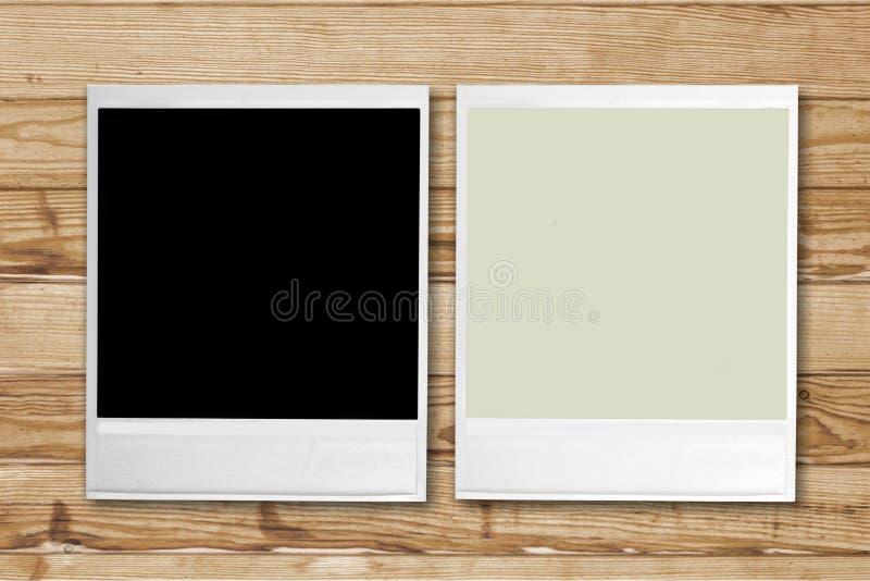 Leere Retro- Fotorahmen auf hölzernem Hintergrund lizenzfreies stockfoto