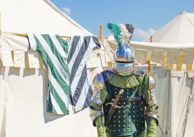 Leere Ritter ` s Rüstung vor weißen Zelten im Hintergrund stockfoto