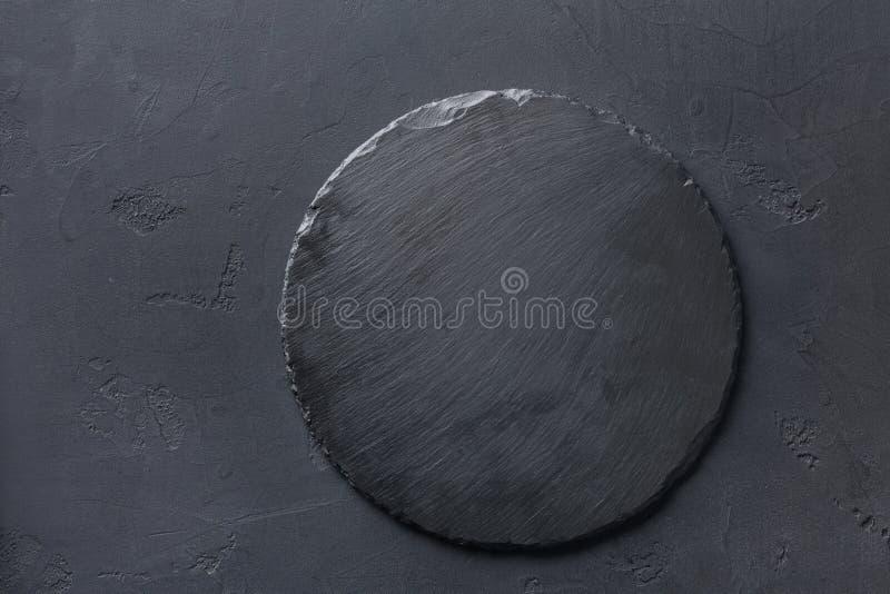 Leere rustikale schwarze Schiefersteinplatte auf dunklem Hintergrund stockfoto