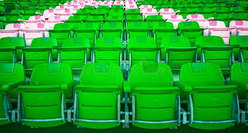 Leere schöne hellgrüne und rosa Stadionssitzplastikreihen in einem Fußballstadion Bunte verwitterte Stühle stockbild