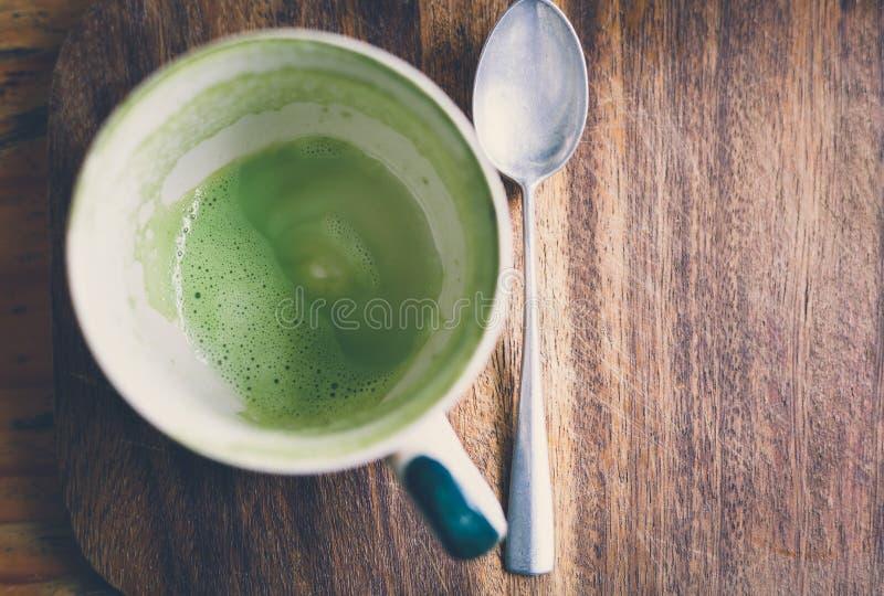 Leere Schale des grünen Tees matcha Latte auf einem hölzernen Brett lizenzfreie stockfotos