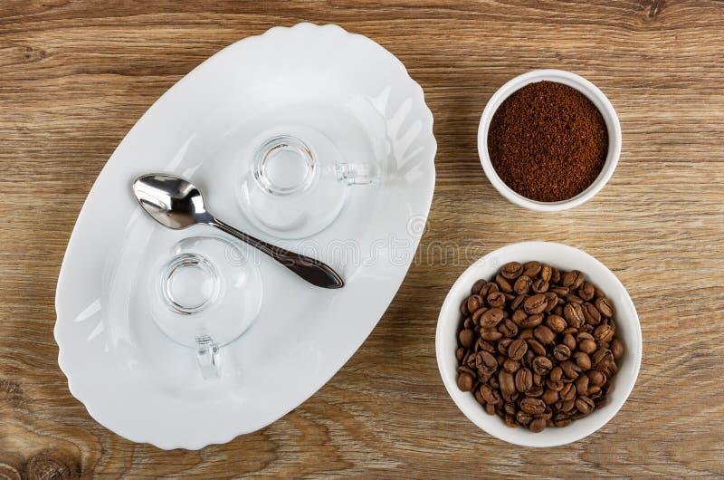 Leere Schalen, L?ffel im Teller, Sch?ssel mit R?stkaffeebohnen, Sch?ssel mit gemahlenem Kaffee auf Holztisch Beschneidungspfad ei lizenzfreies stockbild