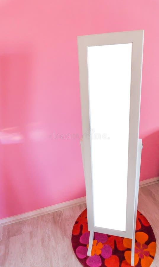 Leere leere Spiegelstellung in einem wenig Prinzessinmädchenraum mit rosa Wandhintergrund und -raum, fallenzulassen, was überhaup lizenzfreies stockbild