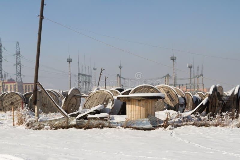 Leere Spulen von Kabeln auf dem Gebiet hinter dem Zaun lizenzfreie stockfotos