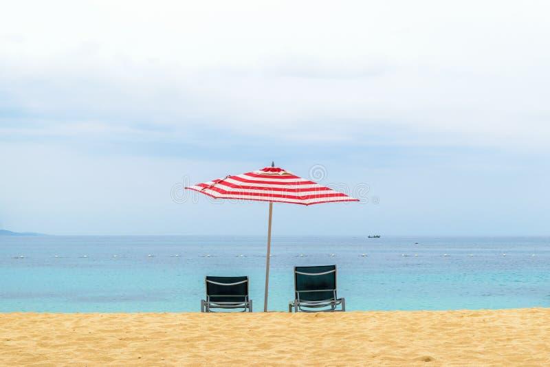 Leere Stühle unter rotem und weißem Regenschirm auf tropischem Strand lizenzfreie stockbilder