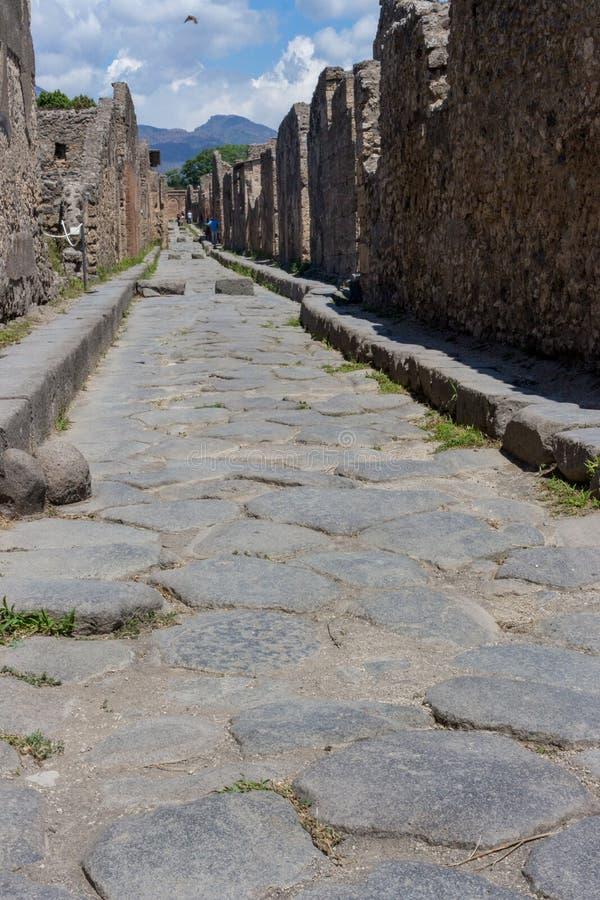 Leere Steinstraße mit Ruinen in Pompeji, Italien Antike Straße in der italienischen alten Stadt gegen Berg Verlassene Straße lizenzfreie stockbilder