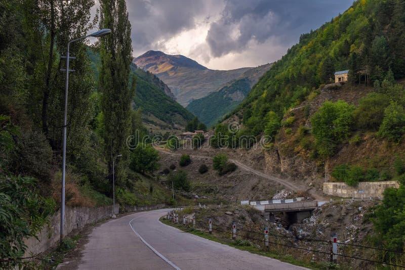 Leere Straße in den Bergen von Svaneti Georgia mit Abfall unter Brücke lizenzfreie stockbilder