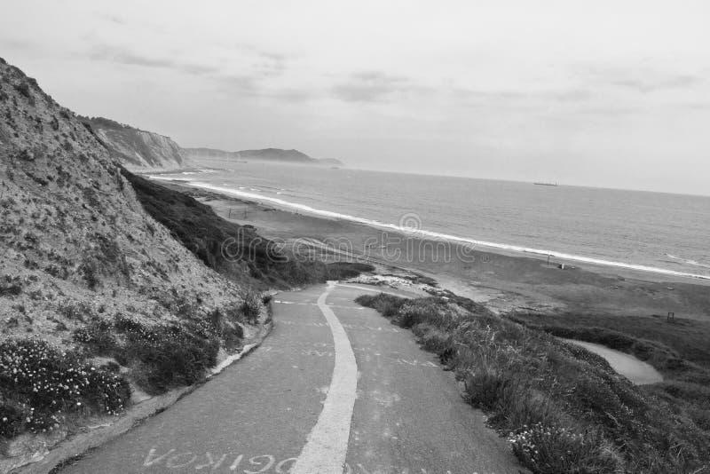 Leere Straße, die unten auf azkorri Strand im Schwarzweiss--, baskischen Land, Spanien führt stockfotografie