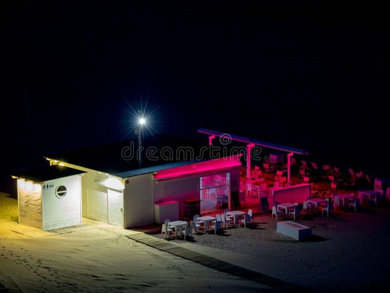 Leere Strandbar mit Bar und Stühle und Tabellen beleuchtete mit den rosa und weißen Lichtern nachts stockfotografie