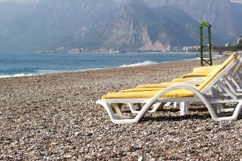 Leere Strandstühle auf dem Strand nahe blauem Wasser, Kemer, die Türkei, Mittelmeer lizenzfreie stockfotos