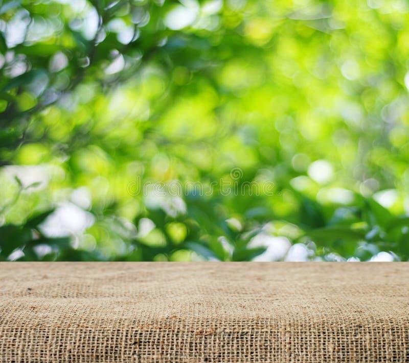 Leere Tabelle bedeckt mit Sackleinen über unscharfen Bäumen mit bokeh Hintergrund stockbild
