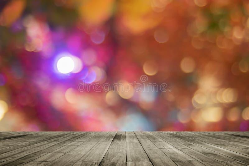 Leere Tabelle des hölzernen Brettes vor buntem unscharfem Hintergrund Braunes Holz der Perspektive über bokeh Licht stockbild