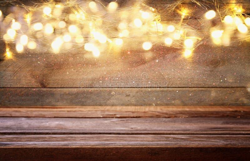 leere Tabelle vor Weihnachtswarmer Goldgirlande beleuchtet lizenzfreie stockbilder