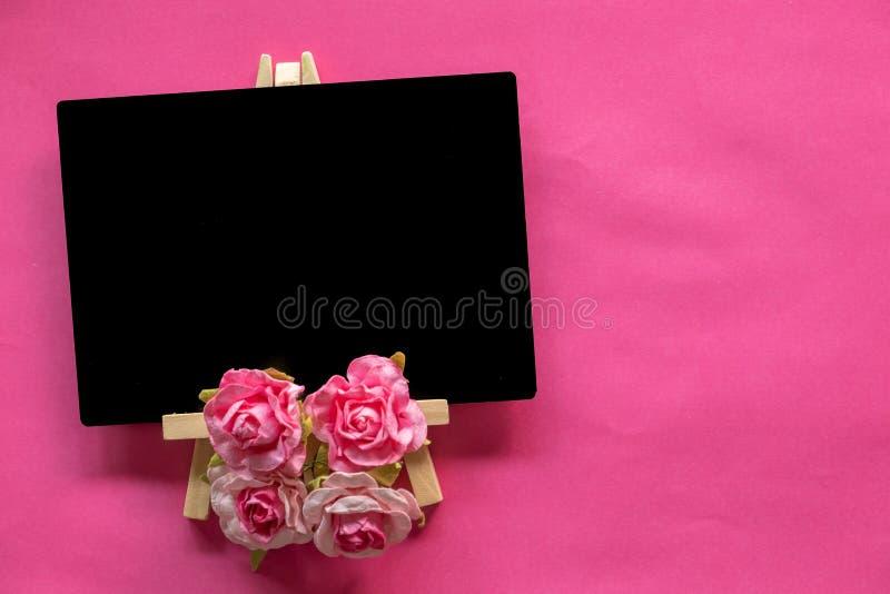 leere Tafel und rosa Blume auf rosa Hintergrund mit Kopienraum, Valentinsgruß-Tageskonzept stockbilder