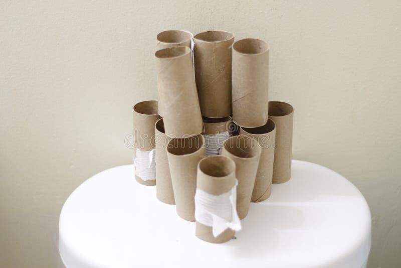 Leere Toilette Rolls kommen auf der Rückseite einer Toilette voran lizenzfreies stockbild