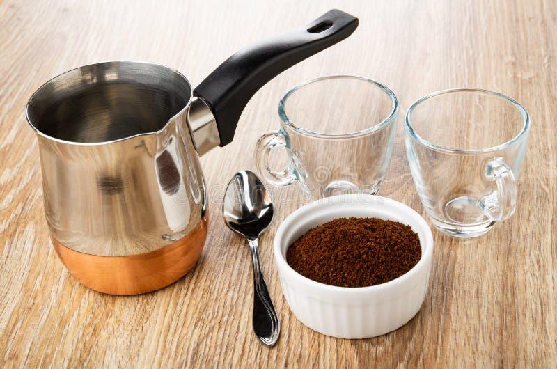 Leere transparente Schalen, cezve, Löffel, Schüssel mit gemahlenem Kaffee auf Tabelle stockbilder