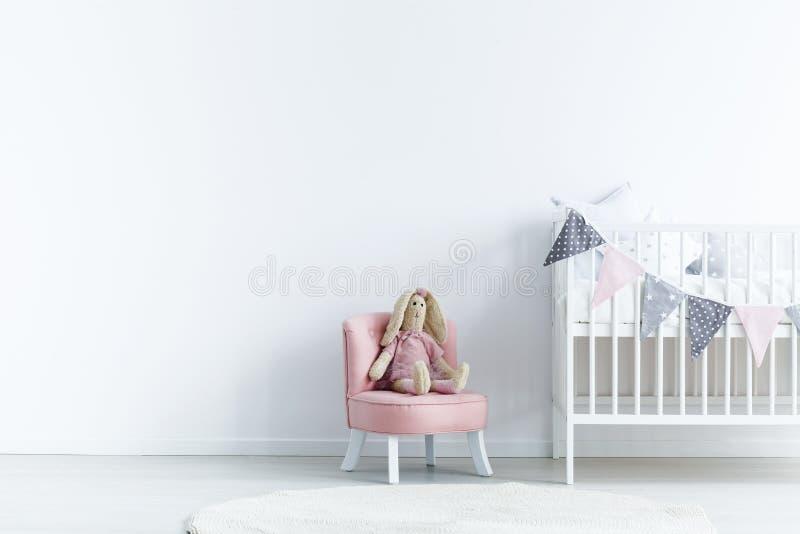 Leere Wand als Nächstes a zum Stuhl mit einem Kaninchen und einer Krippe mit Dreiecken stockfotografie