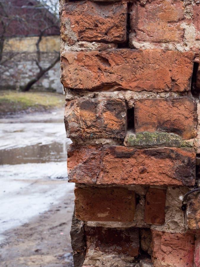 Leere Wand-Beschaffenheit des Weinlese-roten Backsteins Errichtende Fassade mit dem Kratzer-Schaden im Freien, regnerischer Tag stockbilder
