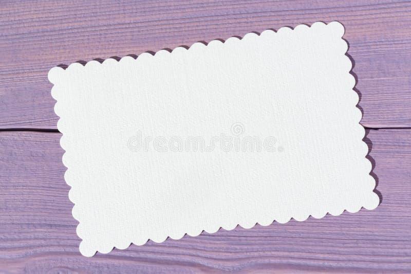 Leere weiße dargestellte Papierkarte auf einem hellvioletten hölzernen Hintergrund lizenzfreies stockbild
