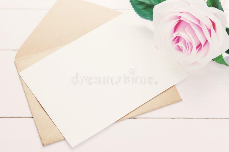 Leere weiße Grußkarte mit brauner Umschlag- und Purpurrose stockfotografie