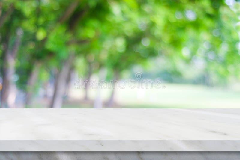 Leere weiße Marmortabelle über Unschärfegrün-Naturparkhintergrund, lizenzfreie stockfotografie