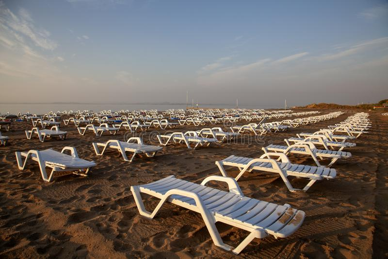 Leere weiße Plastikklappstühle auf Sandy Beach lizenzfreie stockfotos