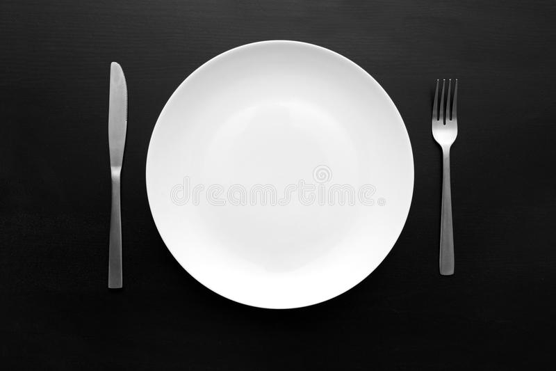 Leere weiße Platte auf dunkler hölzerner Tabelle stockfotos