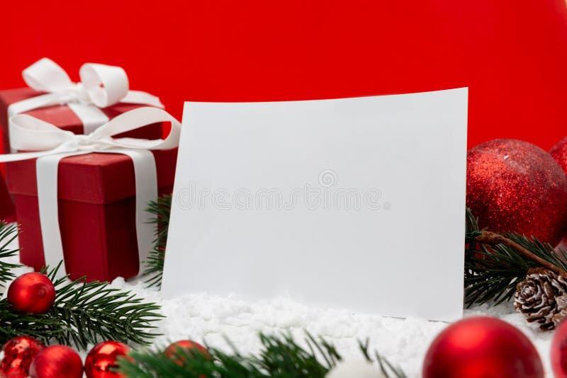 Leere Weihnachtsfeiertags-Grußkarte auf einem roten Hintergrund stockbilder