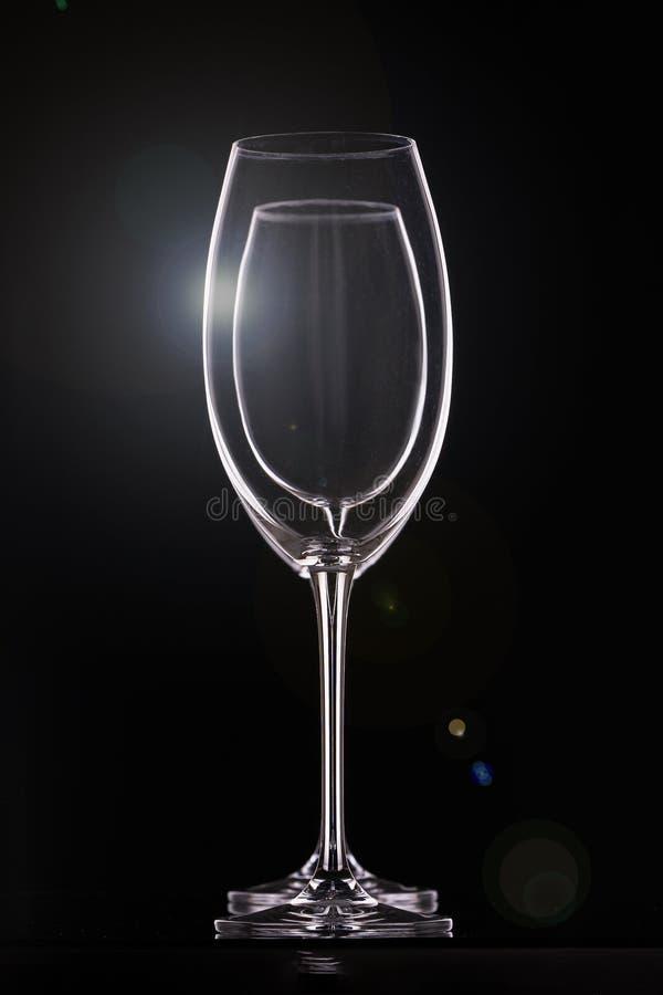 Leere Weingläser auf schwarzem Hintergrund, Glaswaren für Getränke Konturen und heller greller Glanz, vertikale Anordnung lizenzfreie stockfotos