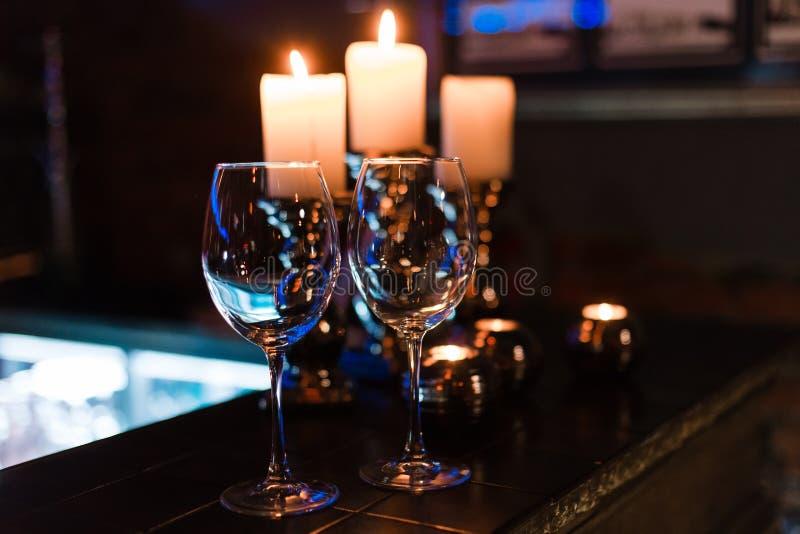 Leere Weingläser und -kerzen mit Beleuchtungslichthintergrund lizenzfreies stockfoto