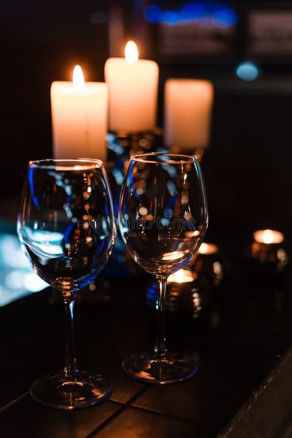 Leere Weingläser und -kerzen mit Beleuchtungslichthintergrund stockbild
