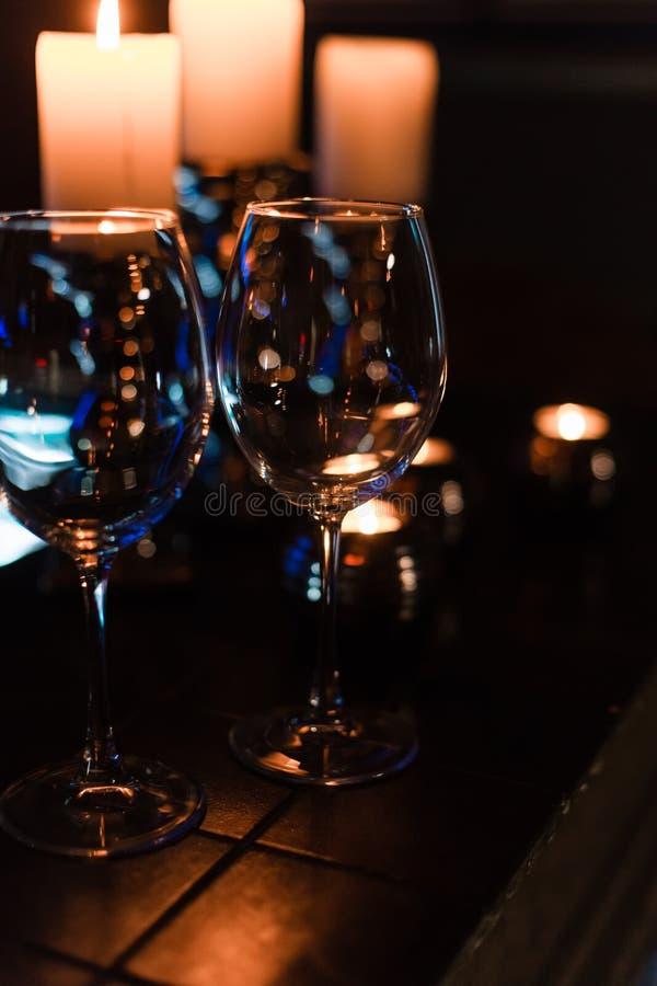 Leere Weingläser und -kerzen mit Beleuchtungslichthintergrund lizenzfreies stockbild