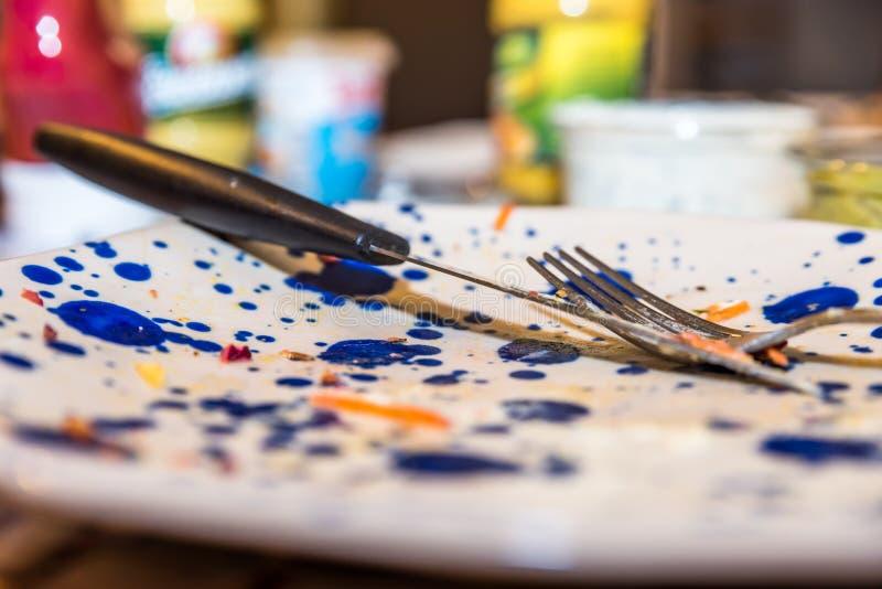 Leeren Sie benutzte bunte Platte mit Gabellöffel und -messer nach dem Lebensmittel, das auf hölzernem Abendtische gegessen wird stockfotografie