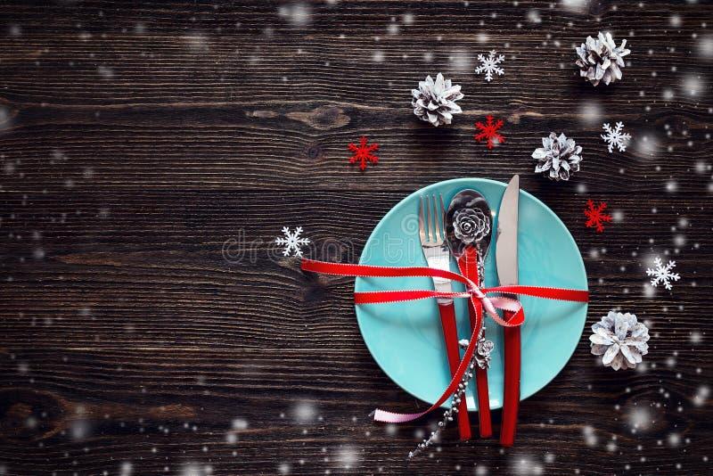 Leeren Sie blaue Platte, Messer, Löffel und Gabel mit rotem Band, christm stockfotografie