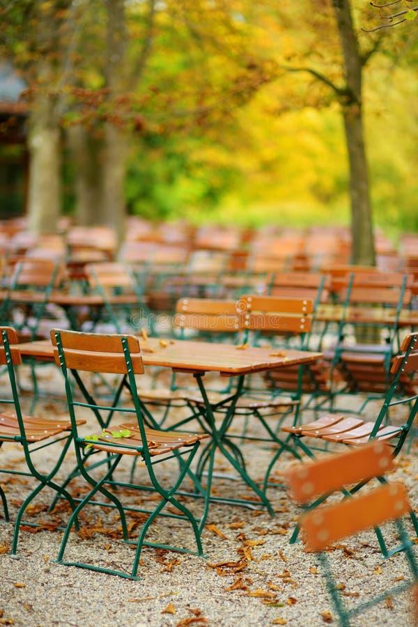 Leeren Sie Café im Freien am Herbsttag in München, Deutschland Leere chiars und Tabellen unter Kastanienbäumen in der Herbstsaiso stockbild