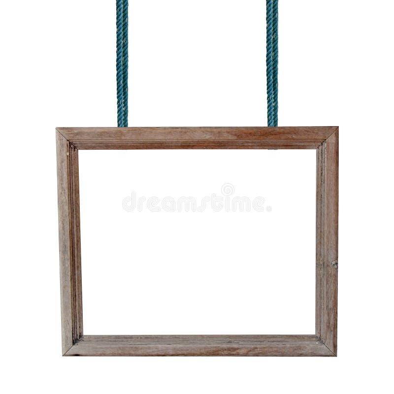 Leeren Sie den Holzrahmen, der an einem Seil auf weißem Hintergrund hängt stockfotografie