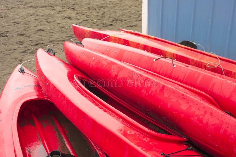 Leeren Sie die roten entspannenden Plastikkajaks für Miete oder Miete, gespeichert auf Überstunden des sandigen Strandes an einem lizenzfreies stockbild