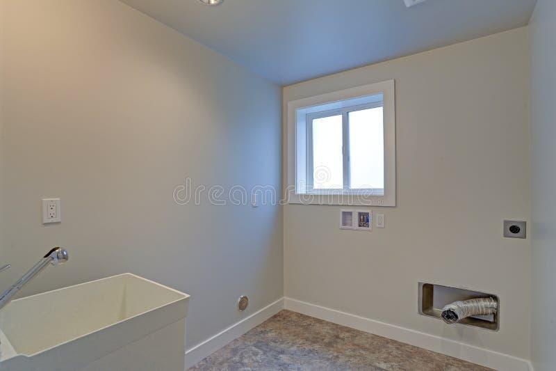 Leeren Sie erneuerte Waschküche mit weißen Wänden stockbilder
