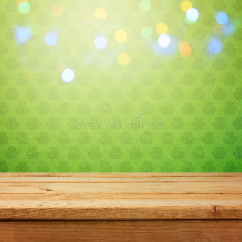 Leeren Sie hölzerne Plattformtabelle über grünem Shamrocktapetenhintergrund mit bokeh Lichtüberlagerung Konzept St Patricks Tages stockfotografie