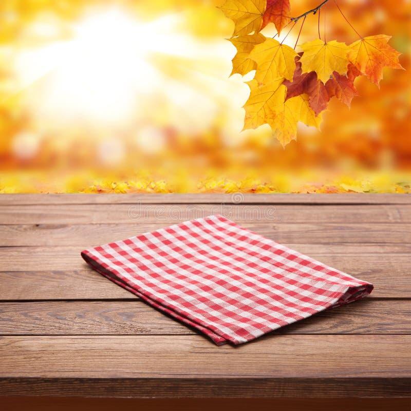 Leeren Sie hölzerne Plattformtabelle mit Tischdecke über bokeh Herbstlaub lizenzfreies stockfoto