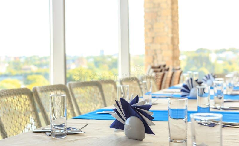 Leeren Sie halb-gedienten Bankettisch im Restaurant mit Servietten, Gläser, Gabeln, Messer, flache DOF-Ansicht gegen verwischt lizenzfreie stockbilder