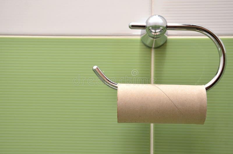Leeren Sie Rolle auf Toilettenpapierhalter mit den weißen und grünen Fliesen im Hintergrund lizenzfreie stockfotografie